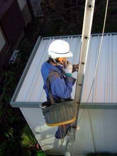 家の外から光ファイバーを入れるべく梯子を登る作業員さん